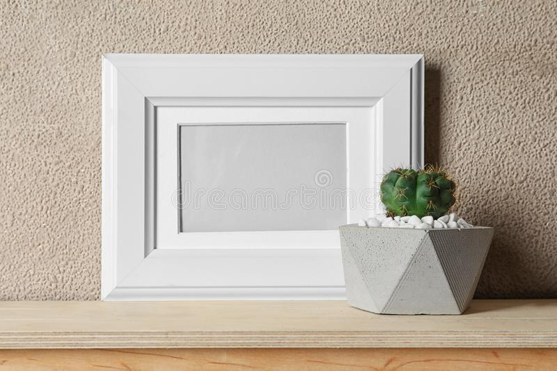 Blank frame and succulent plant on wooden  near brown wall, space for design. Home decor. Blank frame and succulent plant on wooden table near brown wall, space stock photo