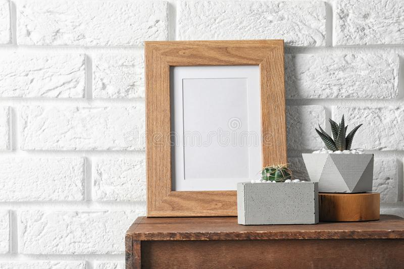 Blank frame and succulent plants on wooden cabinet near white brick wall, space for design. Home. Decor stock images