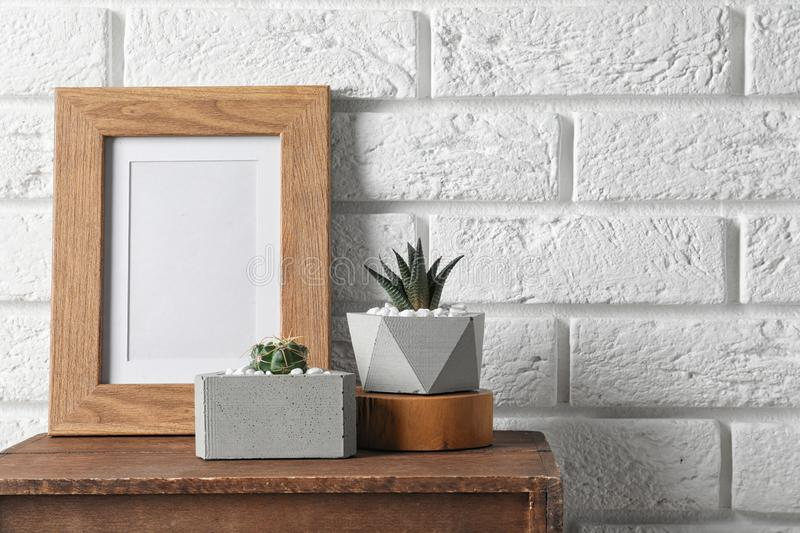 Blank frame and succulent plants on wooden  near white brick wall, space for design. Home decor. Blank frame and succulent plants on wooden cabinet near white stock images