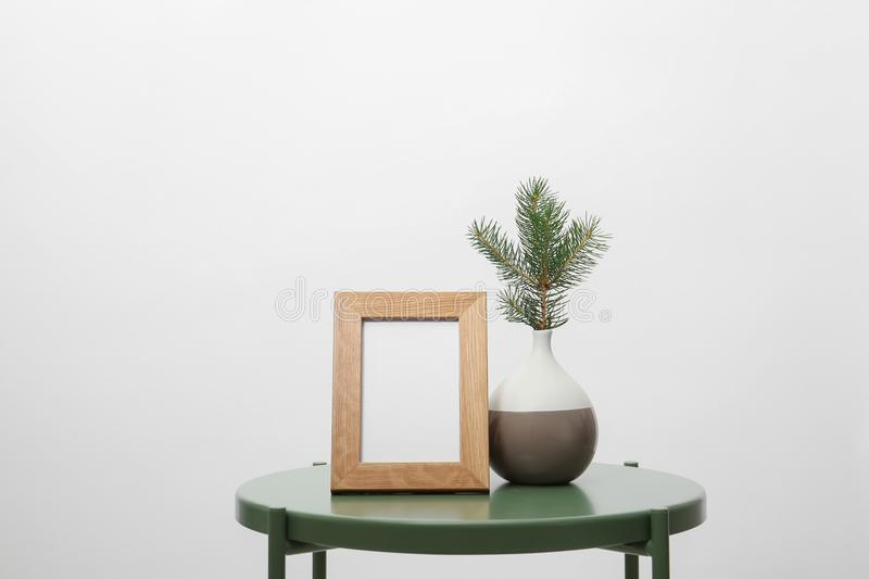 Blank frame and vase with fir branch stock photography