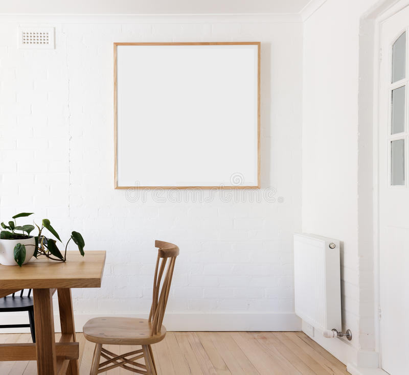 Blank framed print on white wall in danish styled interior dining room stock image