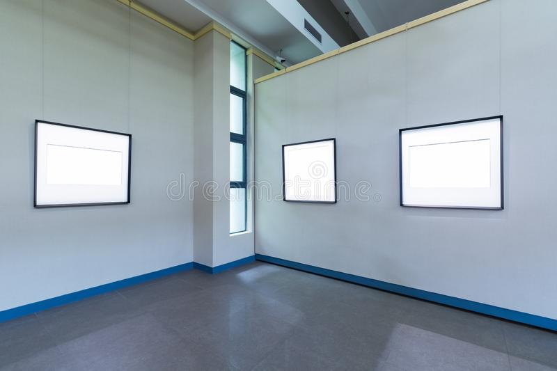 Blank frames on exhibition room. Fro painting or photography on wall, clipping path included stock photos