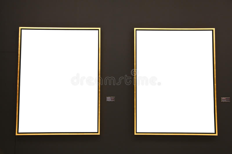 Blank gold painting frames on black wall. For photo editing stock photography