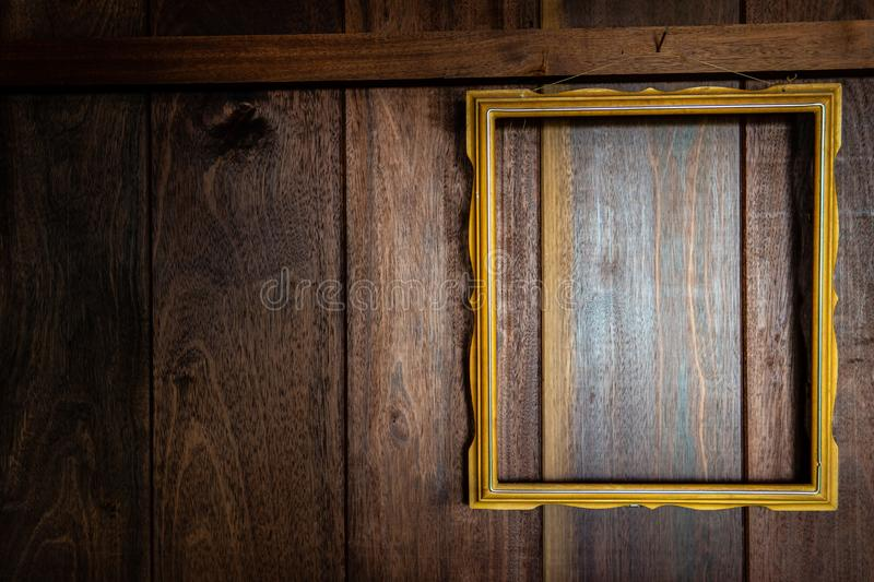 Gold frame hanging on wooden panel wall stock images