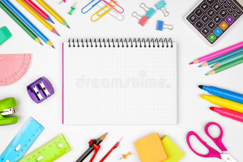 Blank graphing paper notebook with school supplies frame against white with copy space. Back to school. royalty free stock photos