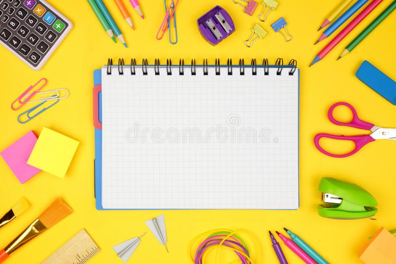 Blank graphing paper notebook with school supplies frame against yellow. Back to school. Copy space. royalty free stock image