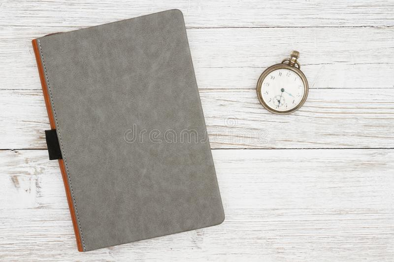 Blank gray journal with pocket watch on a weathered whitewash wood background stock photos