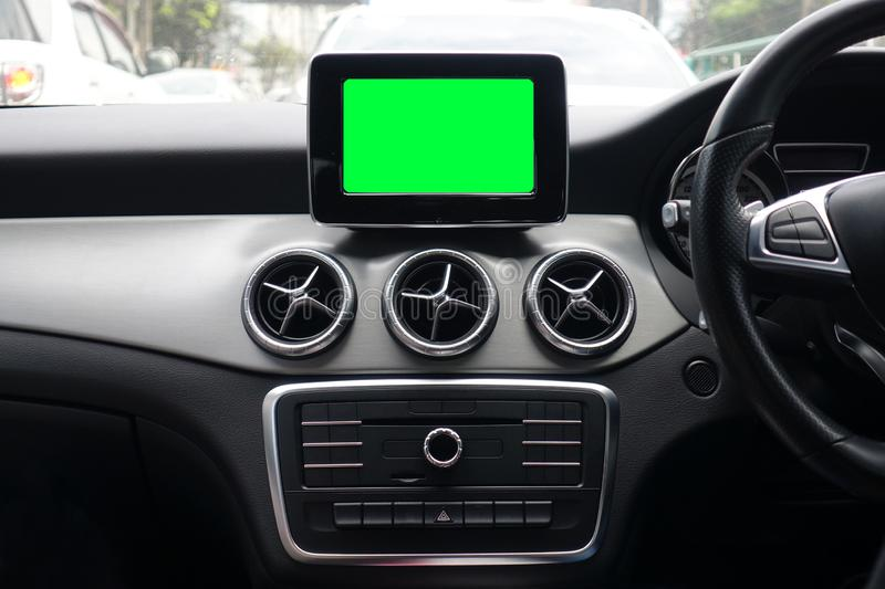 Blank green screen of monitor inside a modern car interior using for navigation maps and GPS in transportation and travel concept. Mock up royalty free stock image