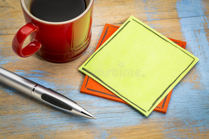 Blank green sticky note with coffee. Blank green sticky note with a pen and a cup of coffee royalty free stock image