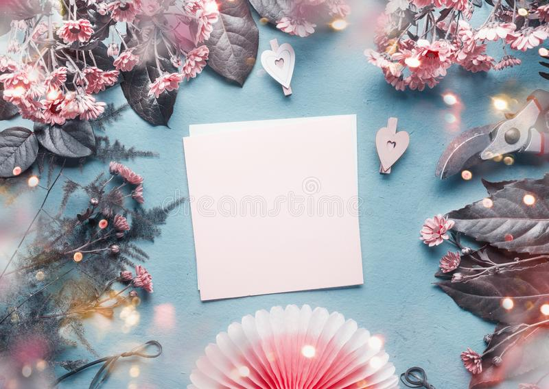Blank greeting card on blue florist desk with pink flowers, hearts and paper origami fan. Abstract greeting concept. Mothers day, stock images