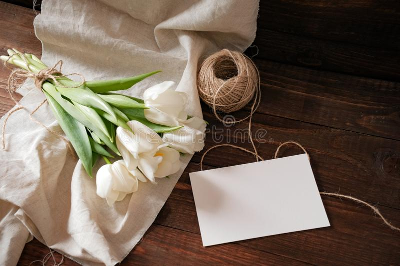 Blank greeting card with bunch of spring flowers on natural wooden table background. Wedding card invitation, tender womans day co. Mposition, bouquet of tulips stock photos