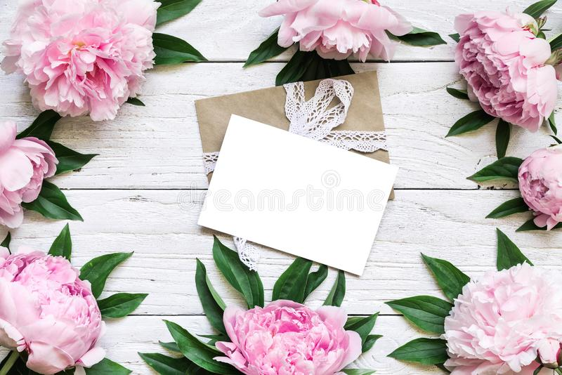 Blank greeting card iand envelope in frame made of pink peony flowers over white wooden table with copy space. Wedding invitation. top view. flat lay. nature stock photo