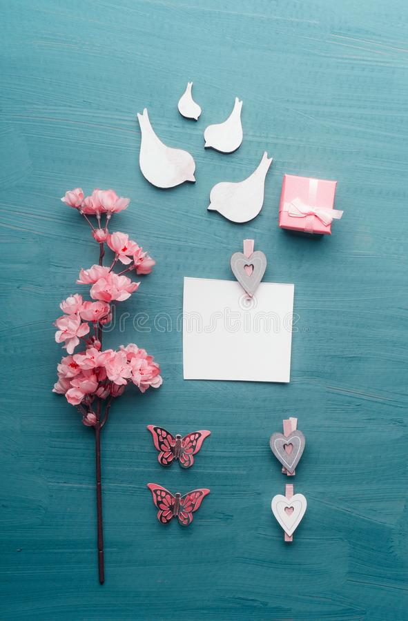 Blank greeting card mock up with pink spring blossom flowers, gift box and decorative bird and hearts, top view. Mothers day or stock photo