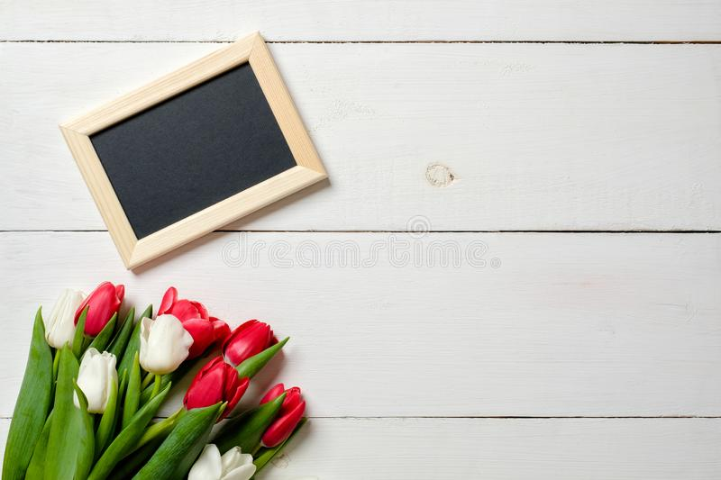 Blank greeting card with tulips flowers on white wooden table. Romantic wedding card, greeting card for womans or mothers day, bir royalty free stock images