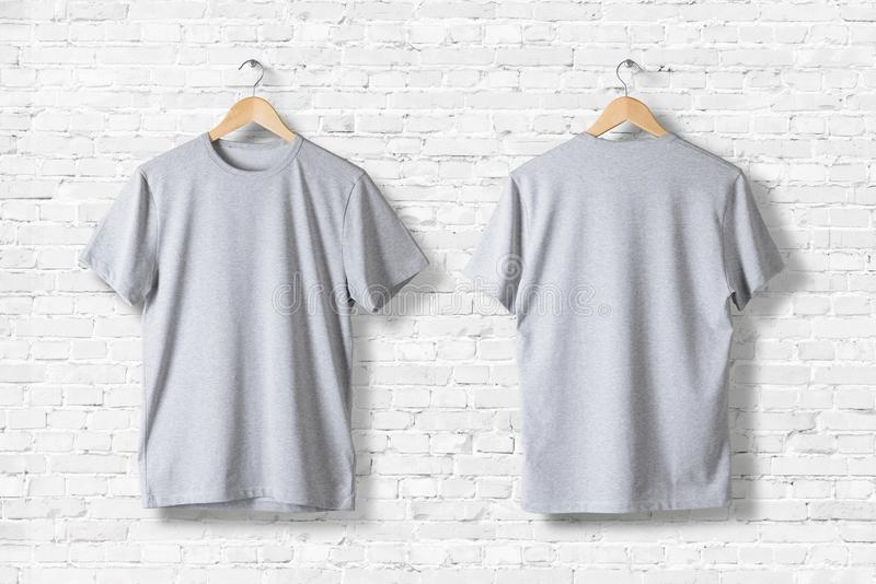 Blank grey T-Shirts Mock-up hanging on white wall, rear and front side view. royalty free stock images