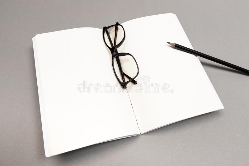 Blank Hard Cover Of Magazine, Book, Booklet, Brochure with pencil and glasses. Mock Up Template Ready For Your Design stock photo