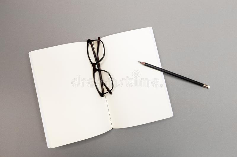 Blank Hard Cover Of Magazine, Book, Booklet, Brochure with pencil and glasses. Mock Up Template Ready For Your Design stock images