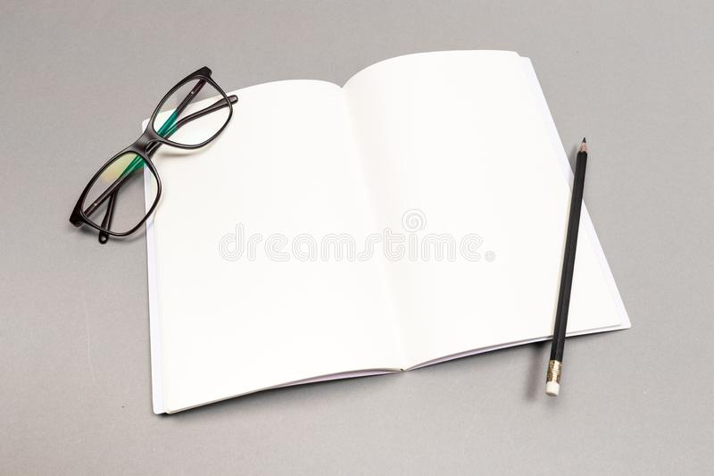 Blank Hard Cover Of Magazine, Book, Booklet, Brochure with pencil and glasses. Mock Up Template Ready For Your Design royalty free stock photo