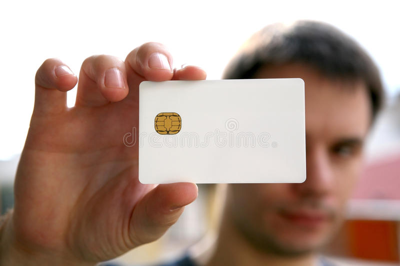 Blank id card. Man holding a blank white card with chip. focus on the card