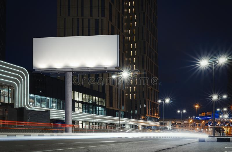 Blank illuminated billboard near well-lit road at night time. 3d rendering stock images