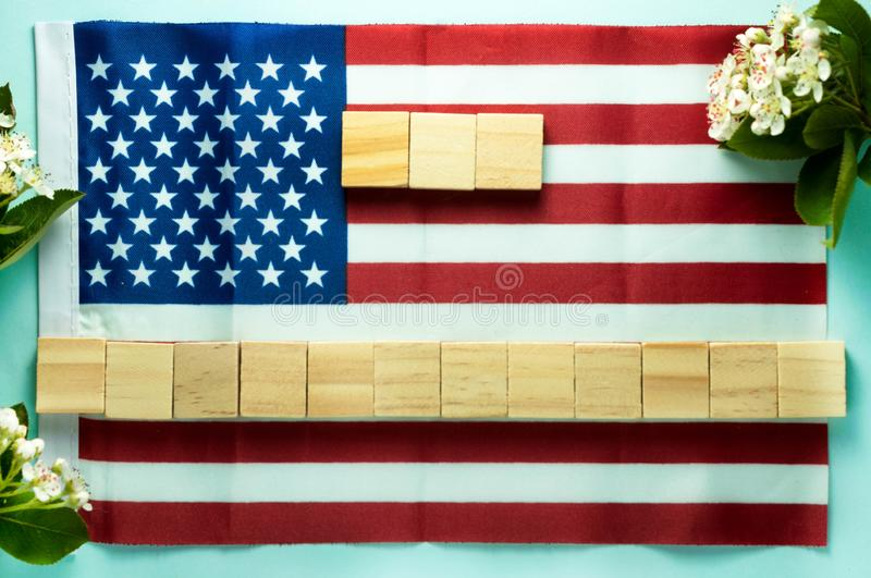 Blank for inscription on fifteen wooden cubes laid out on American flag near blooming branches stock images
