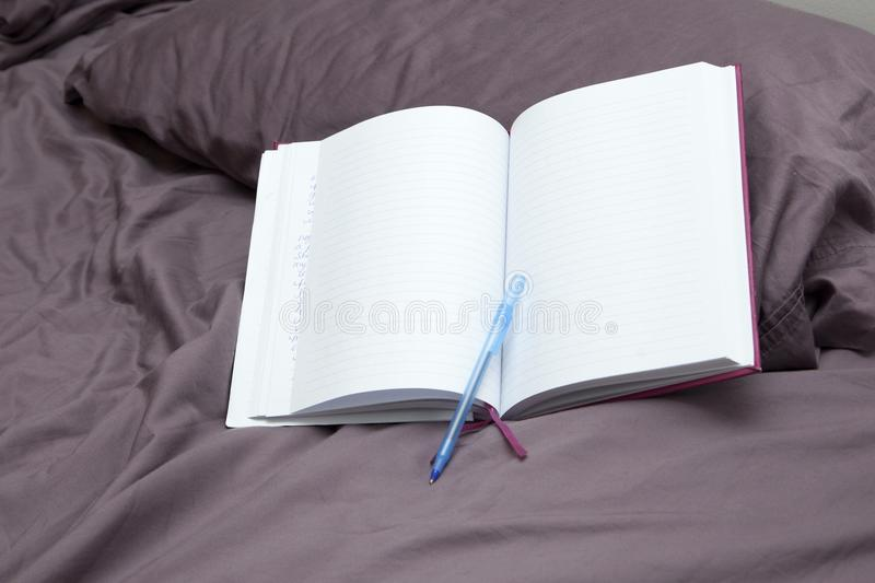 Blank journal or diary. An empty page with pen on a pillow, waiting for a diary entry stock photo