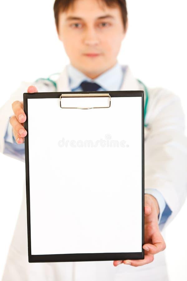 blank läkarundersökning för holding för clipboarddoktorshand arkivfoton