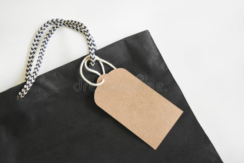 Blank label made of brown paper Strap on black shopping bag. Blank label made of brown paper Strap on black shopping bag and empty space for text royalty free stock images