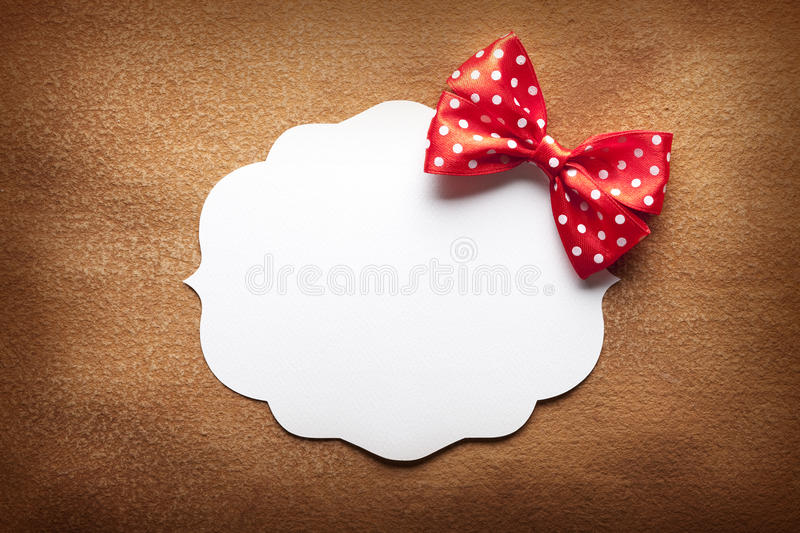 Blank label and red bow on paper background royalty free stock photo