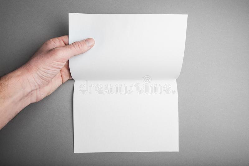 Blank layout open sheet folded 2 times in a hand of a man with soft shadows on a gray background for design royalty free stock photography