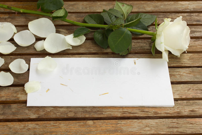 Blank letter with rose. Blank letter with white rose on wooden table royalty free stock photography