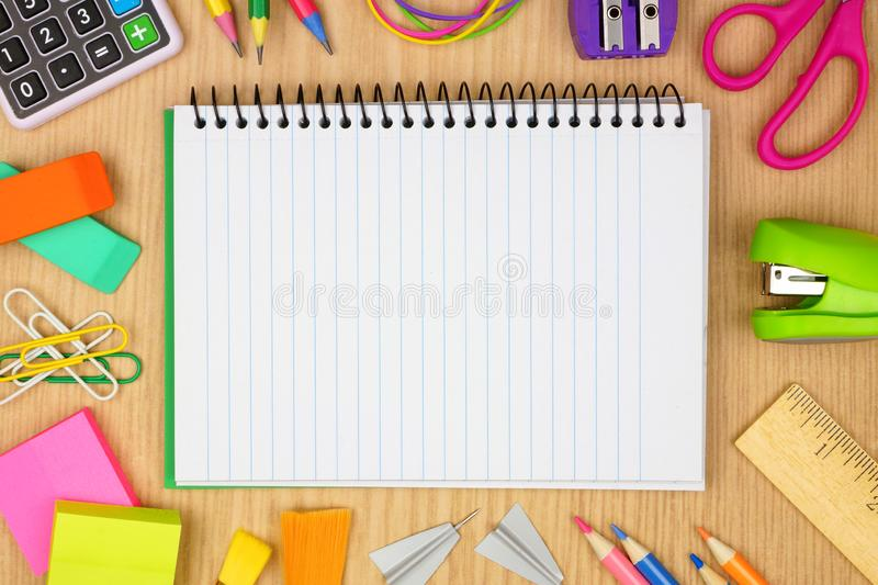 Blank, lined notebook with school supplies frame against a wood desk background with copy space. stock images