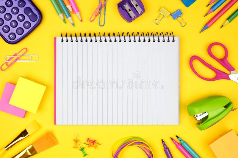 Blank, lined, notebook with school supplies frame against a yellow background. Back to school. Copy space. stock photo