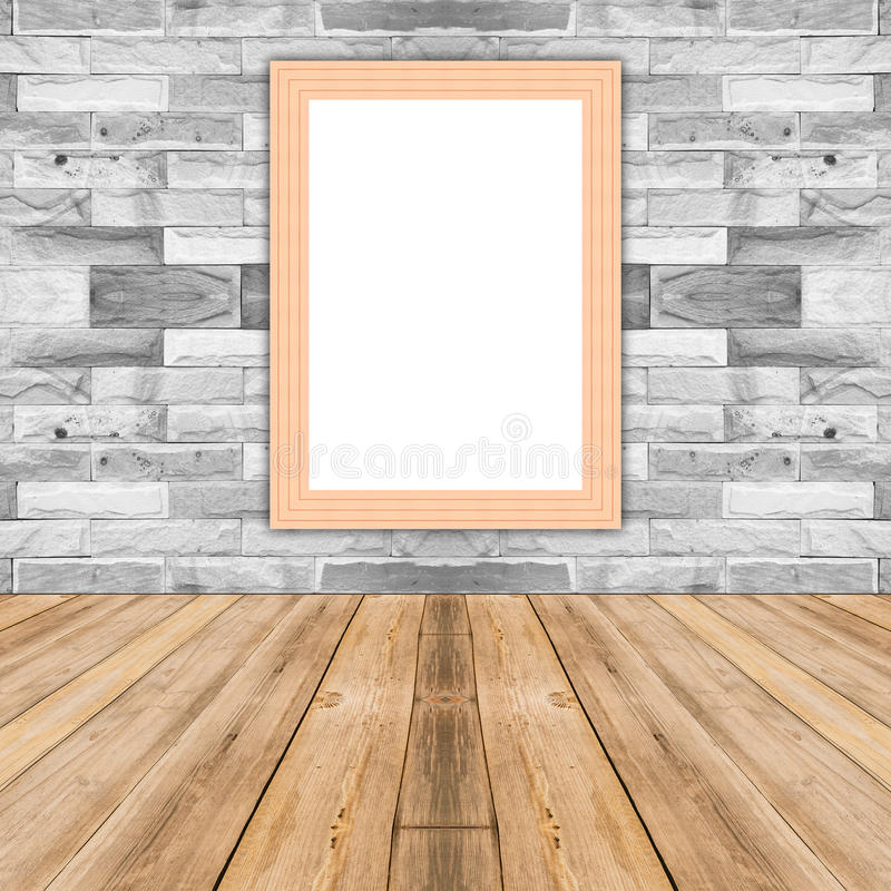 Blank maize wooden photo frame leaning at white brick wall. royalty free stock image