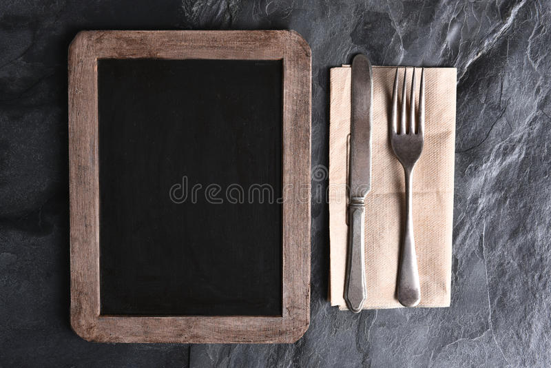 Blank Menu Board and Silverware. High angle view of a blank chalkboard menu next to silverware on a napkin. Strong side light on a slate table royalty free stock photography