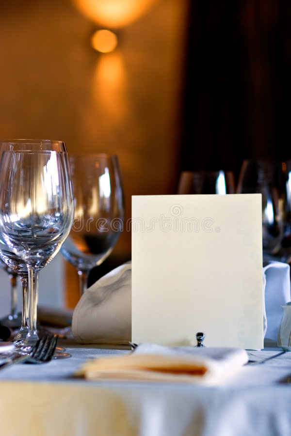 Blank menu on restaurant table. Served table in restaurant interior, with blank menu, with copy space, insert your own information stock image