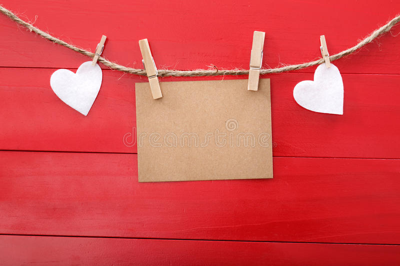 Blank message card and felt hearts with clothespins. Over red wooden board stock photo