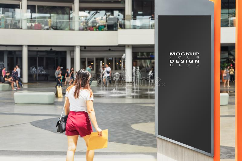 Blank mock up of vertical street poster  advertising billboard in the city for your advertising with blur people in action, Empty royalty free stock photography