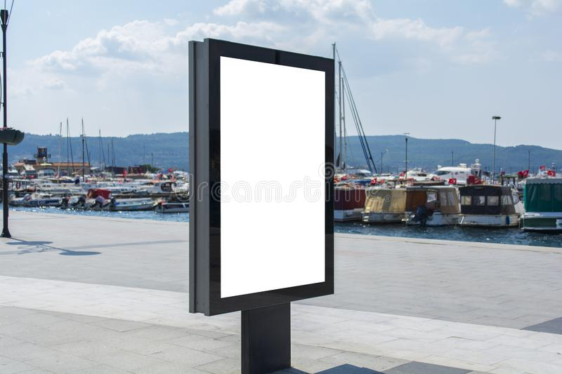 Blank mock up of vertical street poster billboard on marina background in turkey. Blank One Vertical Poster Billboard - Including clipping path around blank area royalty free stock image