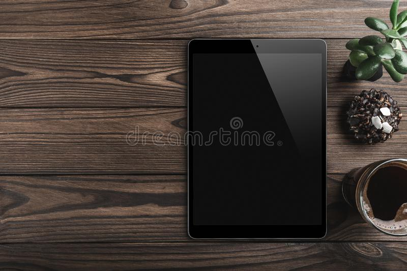 Blank modern digital tablet with coffee cup and green plant on a wooden desk. Top view. royalty free stock photos