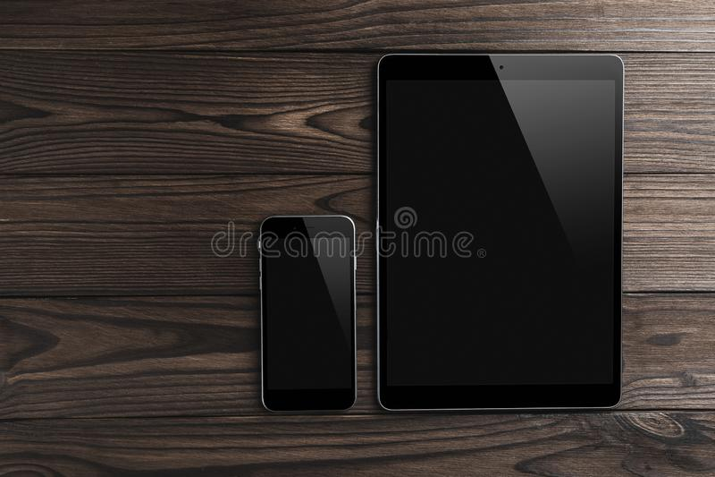 Blank modern digital tablet with phone on a wooden desk. Top view, flat lay. High quality detailed graphic collage royalty free stock photography