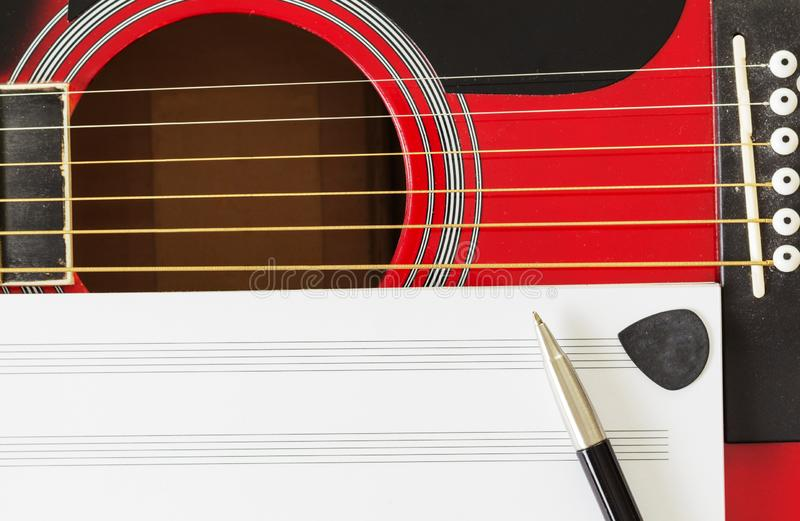 Blank music notebook page with copy-space, on red guitar with six strings. With pen and black guitar pick. Musical education stock images