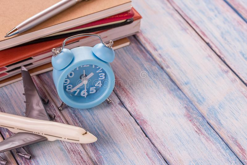 Blank notebook,airplane toy,pen and alarm clock on office desk w stock photos