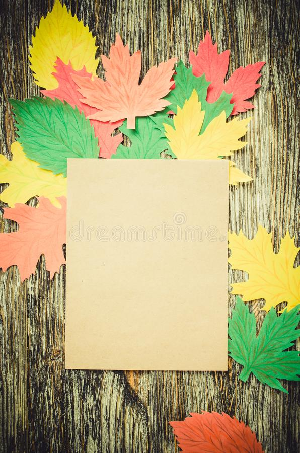 Blank notebook and autumn paper leaves on vintage wooden background. Autumn, fall concept royalty free stock photo