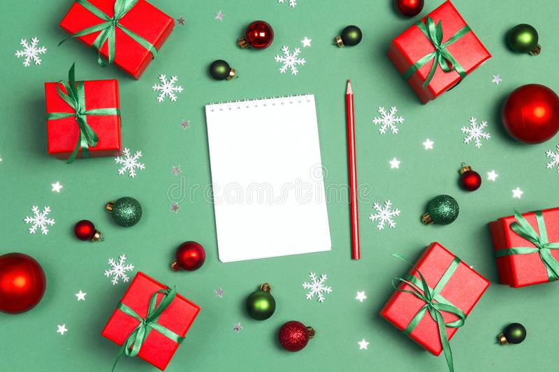 Blank notebook with Christmas composition of gifts  and decoration on a green background. Place for a wish list, gifts or goals royalty free stock images