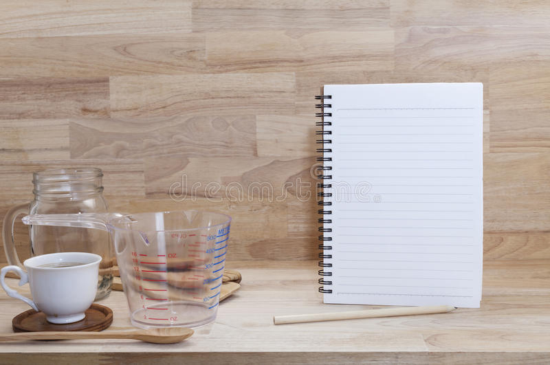 Blank notebook with coffice cup and measuring cup and wooden spoon, cooking supplies on wood background.  stock photo