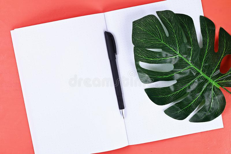 Notebook coral background, tropical leaf. Top view, flat lay. copy space. Summer background, travel. Blank notebook on coral background, tropical leaf. Top view royalty free stock images
