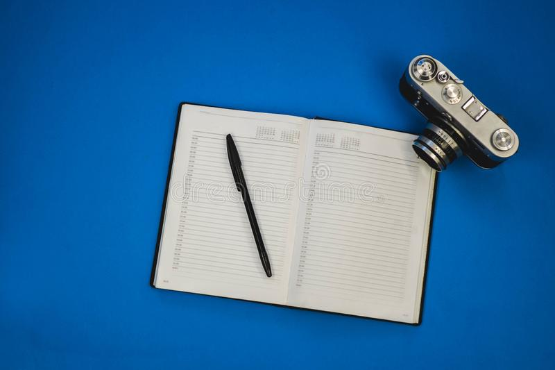 Blank notebook with fountain pen and retro camera on wooden table royalty free stock photo