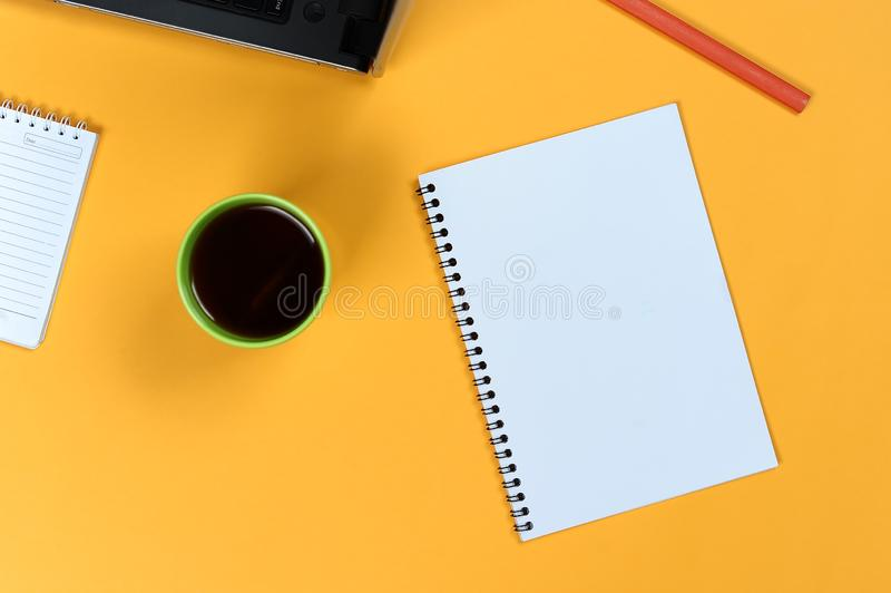 Blank notebook page, laptop, coffee cup and pencil. Blank writing pad for ideas and inspiration royalty free stock images