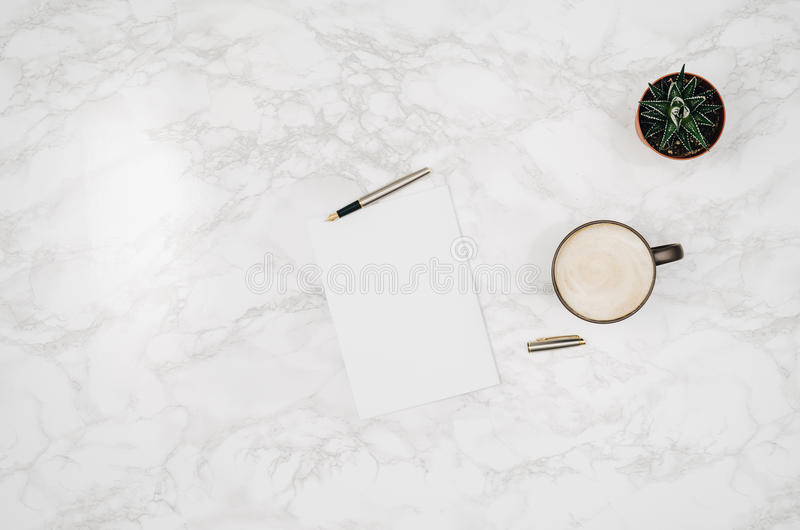 Blank notebook page on white marble table background. Image taken from above, top view. Frame composition with copy space royalty free stock photo